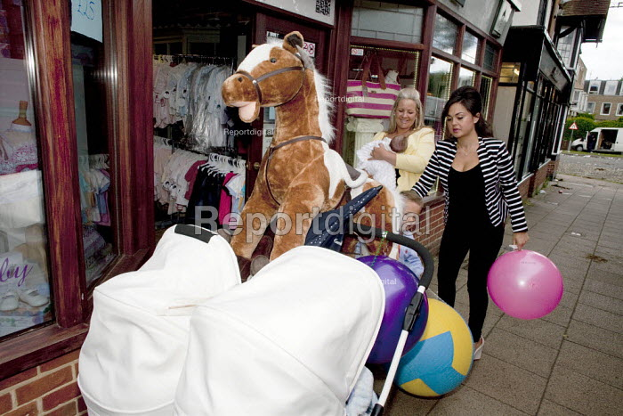 Wickham Horse Fair a traditional one day annual event, Hampshire. A young mother outside a baby clothes shop with a huge soft toy horse with help from her mother holding the families new born baby. - David Mansell - 2015-05-20