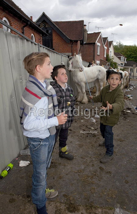 Wickham Horse Fair a traditional one day annual event, Hampshire. Boys playing a game of heads or tails with a coin. - David Mansell - 2015-05-20