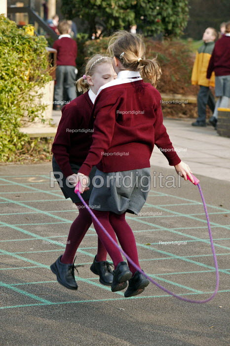 Wedmore First School, a 210 pupil village school in Wedmore, Somerset, run by Somerset LEA. Two school girls seen during their morning break, exercising by using a skipping rope supplied by the school.keeping fit physical exercise - David Mansell - 2005-02-08