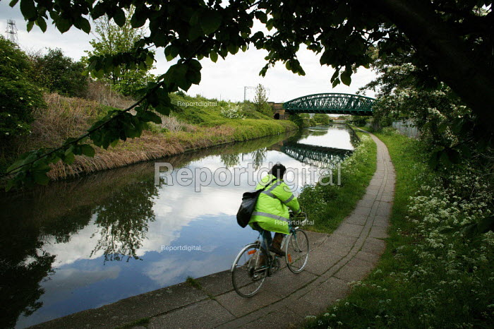 Cycling to work along the towpath of The Grand Union Canal, a Railway bridge crosses the canal. Willesden London - David Mansell - 2005-05-09