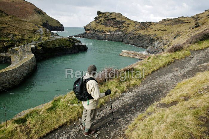 The village of Boscastle, Cornwall, positioned on the North Cornish coast. An elderly male retired walker is seen starting off on his coastal walk in view of the harbour entrance. - David Mansell - 2005-03-08