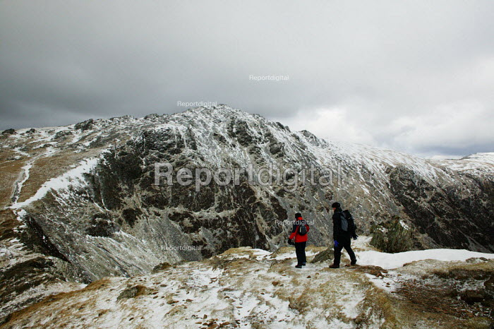 Two walkers, man and woman carrying their day backpacks walking along the route to climb Cader Idris mountain, 892 metres high, situated in the Snowdonia National Park, North Wales. - David Mansell - 2005-03-12