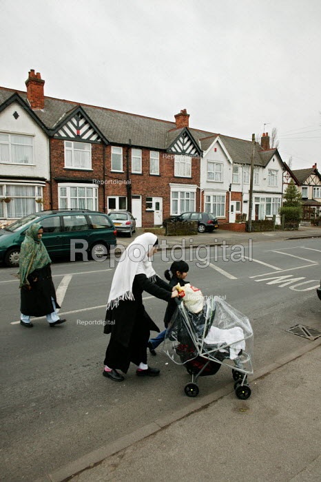 Inner city suburb of Birmingham, Sparkhill, Muslim mother pushing her pram walking with her young children from school. - David Mansell - 2005-03-15