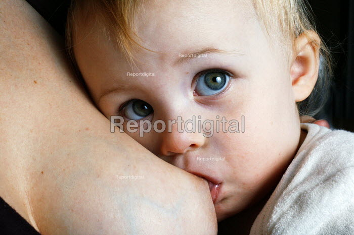 A mother is seen naturally breast feeding her two year old child. - David Mansell - 2005-11-15