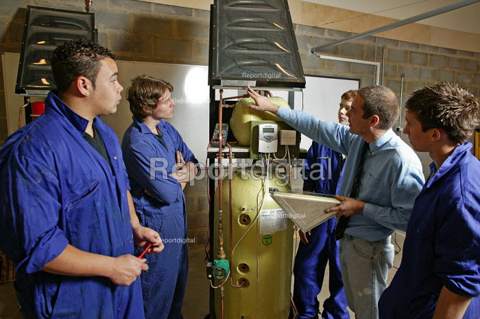 A college lecturer is seen lecturing further education students FE who are studying a vocational course in solar heating, at Bedford College, Bedfordshire, it is only one of two courses in the whole of the UK to offer this type of training to young trainee plumbers. Plumbers of the future will have to be able to instal solar heating panels to households to help reduce the amount of fossil fuel used, due to the high cost of electricity and to the threat of global warming. - David Mansell - 2005-11-24