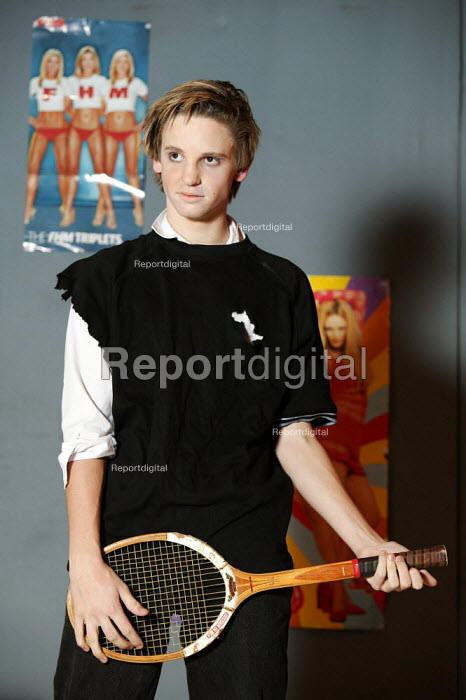 Angry adolescent young man, pretending to be a rock star by using a tennis racket as a guitar. 