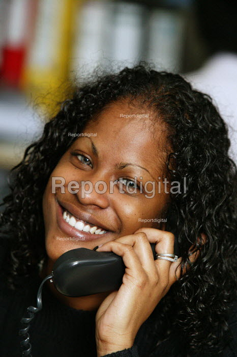 City office workers at work in their offices at CB Richard Ellis, the world's largest property estate agents based in the square mile of the City of London. A smiling and happy young woman who works in the accounts department seen on the telephone. - David Mansell - 2006-04-09