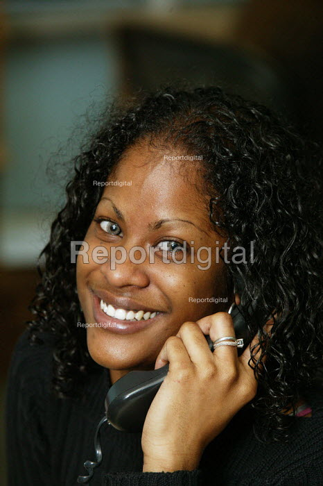City office workers at work in their offices at CB Richard Ellis, the world's largest property estate agents based in the square mile of the City of London. A happy and smiling young woman who works in the accounts department seen on the telephone. - David Mansell - 2006-01-09