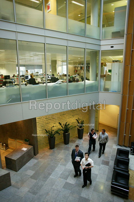 Office workers at work in their offices at CB Richard Ellis, the world's biggest property estate agents based in the square mile of the City of London. Looking down onto people walking past in the lobby of the ground floor of the building. - David Mansell - 2006-04-09