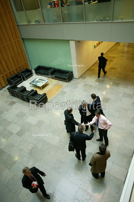 Office workers at work in their offices at CB Richard Ellis, the world's biggest property estate agents based in the square mile of the City of London. Looking down onto people meeting each other in the lobby of the ground floor of the building. - David Mansell - 2006-01-10
