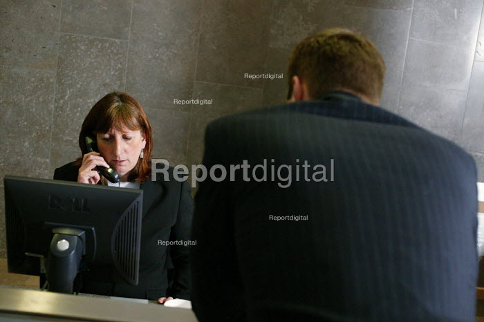 City office workers at work in their offices at CB Richard Ellis, the world's largest property estate agents based in the square mile of the City of London. A visitor arrives at the reception desk, where the receptionist is dealing with his inquiry. - David Mansell - 2006-01-09