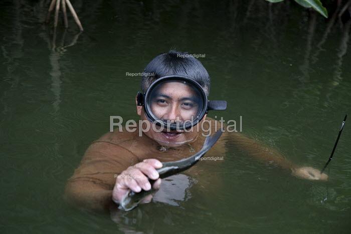 A fisherman having caught a fish, Manialtepec Lagoon on the coast of Oaxaca, a mangrove swamp with a great biodiversity, Mexico. - David Bacon - 2008-11-07