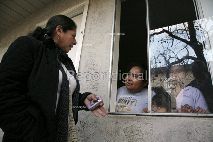Mixtec Activist living in an apartment complex in Santa Maria, talking to neighbouring family. - David Bacon - 2009-02-15