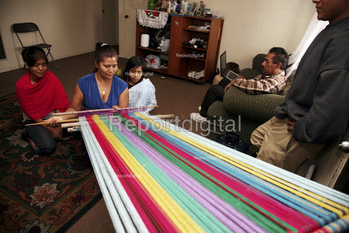 Santa Paula, California. The family of Miguel Alonso are Purepecha migrants from Turicuaro in the Mexican state of Michoacan. Consuelo Alonso shows her two daughters how she weaves a multi-colored rebozo, a traditional garment on her loom. The girls wear rebozos woven by their mother. - David Bacon - 2009-04-24