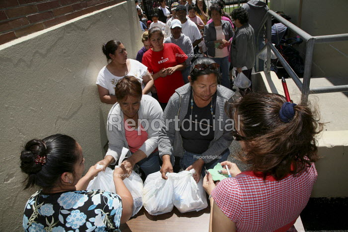 Hungry families get food at a food distribution centre, Greenleaf Elementary School, Oakland, California, USA. The food bags are donated by a Christian Faith Network. Many people have jobs but don't make enough money to buy food, many are Mexican immigrants - David Bacon - 2009-05-28