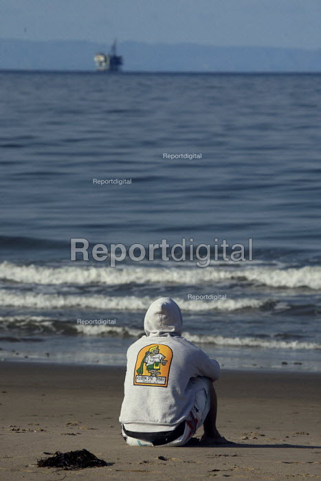A teenager looking out at a oil rig in the Santa Barbara Channel, where a huge oil spill in January 1969 covered the beaches. Today oil companies are pushing again for concessions for oil drilling in the channel. - David Bacon - 2009-06-10