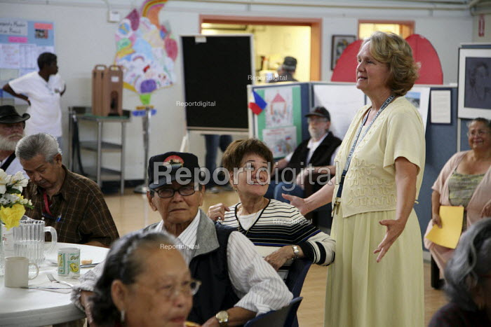 Center director Carol Johnson talks with the elderly. Poor elderly eat lunch at St. Mary's Center in Oakland, California, which provides food for poor people. Food for the program comes from the Alameda County Community Food Bank and Christian charites. - David Bacon - 2009-08-13