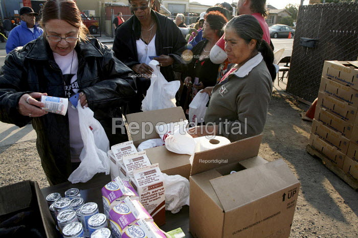 The poor receive bags and shopping carts of food and food parcels at the food distribution. Many families are Mexican immigrants. Food for the program comes from the Alameda County Community Food Bank. The people distributing the food are all Christian volunteers. - David Bacon - 2009-08-15