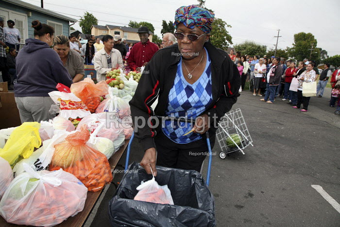 Oakland, California, USA: Food distribution organised every week by The Alameda County Community Food Bank in one of the poorest neighbourhoods in the area. Most recipients are Mexican immigrants and don't have enough money to buy food. The food is bagged and distributed by the same people who receive it - David Bacon - 2009-08-21