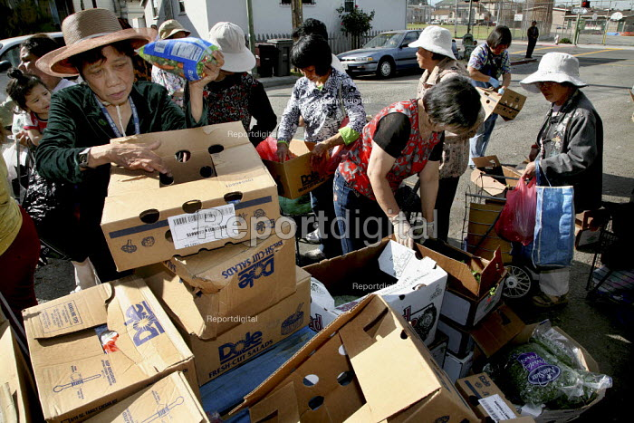 Good Samaritan Food Pantry distributing food to Oakland residents on the sidewalk in front of a house where food is stored and bagged. Before the distribution starts, dozens of people, many of them Chinese and Vietnamese immigrants, line the sidewalk on both sides of the street. East Oakland is one of the poorest neighborhoods in San Francisco . It is staffed by Christian volunteers and demand has dramaticly increased due to the recession. - David Bacon - 2009-08-28