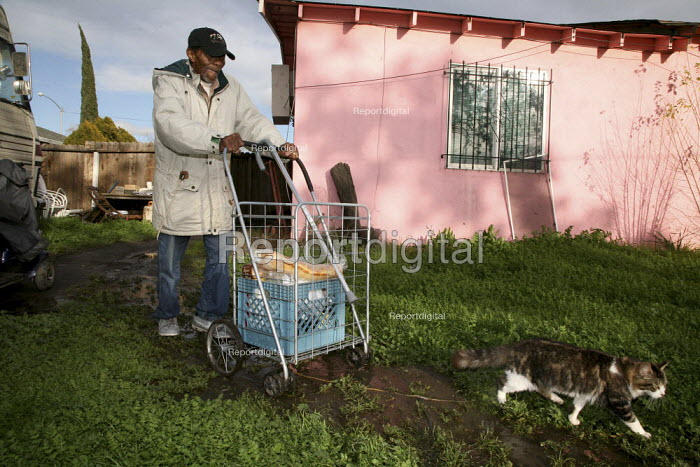 A man returning with his shopping to his trailer in a backyard, in Stockton. - David Bacon - 2010-01-19