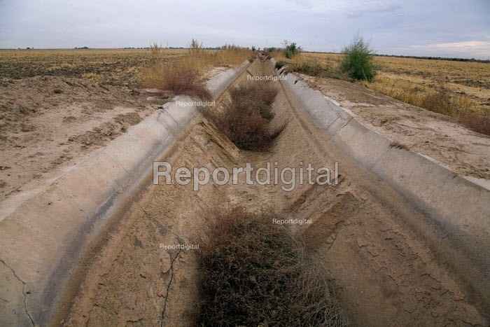 A dry irrigation canal leading to the US Mexico border. In the Yuma Valley hardly any water flows in the old watercourse of the Colorado River, almost all has been diverted to provide water for cities like Las Vegas and Los Angeles, or taken for irrigation water further upstream. Economic development and increased agricultural water use in the USA increased degradation of water quality received by Mexico. Sonoran Desert, Arizona - David Bacon - 2010-12-04