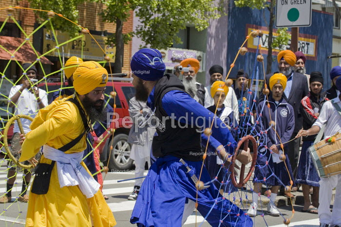 During the parade dancers spin webs of ropes and balls. Sikhs parade through the streets of Berkeley California on the anniversary of the death of Guru Arjan Dev Ji, which is celebrated as a day of peace. - David Bacon - 2011-06-12