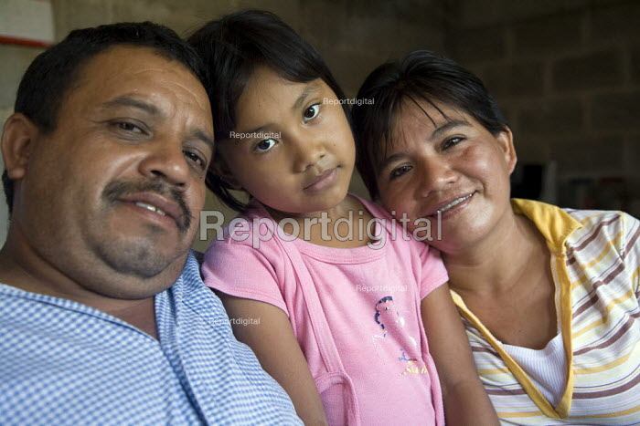 A farmer embraces his wife and daughter at their family... - David Bacon, DNB1110mx04.jpg