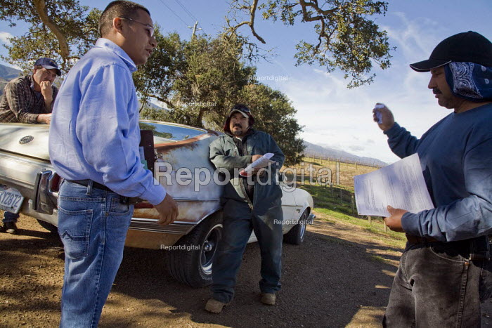 Mariano Alvarez, a community worker for California Rural Legal Assistance, explains to farmworkers working on a vineyard the requirements that contractors must meet - to provide sanitation and drinking water for workers in the fields. Salinas Valley, California USA - David Bacon - 2012-01-26