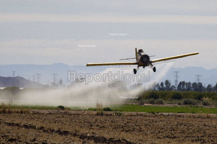 A crop duster spraying pesticides on a field south of Seeley an unincorporated community, in the Imperial Valley, California - David Bacon - 2012-02-04