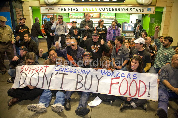 SAN FRANCISCO, California- Workers who serve food at the concession stands at AT&T Park, the baseball park for the San Francisco Giants, sit-in with supporters at the Garlic Fries concession. The workers and their union, UNITE HERE Local 2, protested because the concessionaire won't negotiate a fair contract. After sitting down in front of the concession, several were arrested in an act of civil disobedience. - David Bacon - 2013-06-18