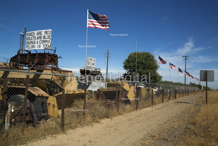 Los Banos, California A junkyard with extreme right wing Tea Party slogans on signs, accusing Obama of being a Communist and lots of U.S. flags - David Bacon - 2013-09-29
