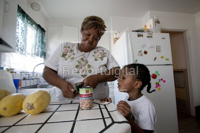 Oakland, California: Opening a can of beans. Grandmother looking after her grandson Tayvion at home with groceries from a food bank in Alameda County. Often her family doesn't have enough money to buy food and pay rent, and has to choose between one and the other. - David Bacon - 2013-11-01