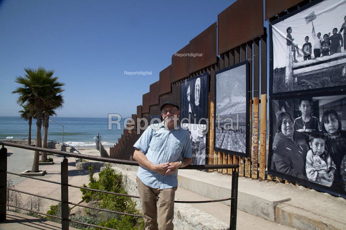 """Tijuana, Mexico, David Bacon photographer infront of his border wall exhibition """"In the Fields of the North"""" - photographs of farmworkers in the U.S., almost all migrants from Mexico. They are hung on the iron bars of the border wall, on the Mexican side of the border wall between Mexico and the U.S. The exhibition was organized by the Colegio de la Frontera (COLEF) and the Centro Cultural de Tijuana (CECUT). - David Bacon - 2014-09-09"""