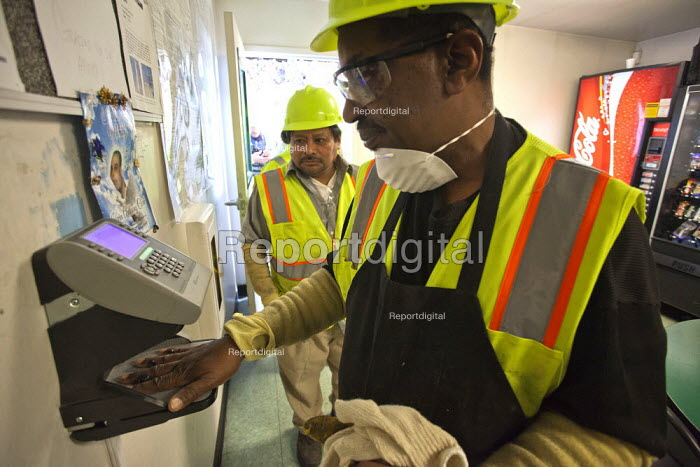 California- Workers at the recycling sorting facility of Alameda County Industries clock on at the start of their shift with a hand scanner Biometric Handscanner clocking in machine - David Bacon - 2015-02-18