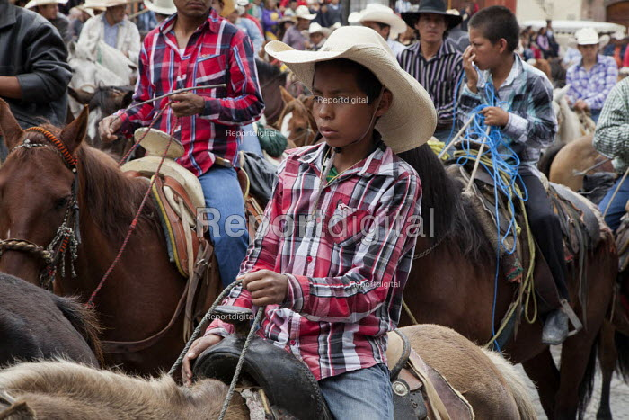 Mexico, Fiesta for St. Michael, the patron saint of San Miguel de Allende. Cowboys parade through the streets on their horses. The horses are then blessed by a priest in front of the church on the main plaza. - David Bacon - 2014-10-03