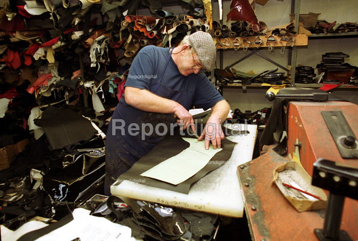 Cobbler cutting out a boot shape from leather. - Duncan Phillips - 2002-01-31