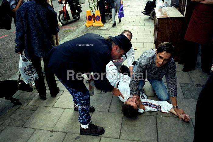 Shop Assistants apprehend a suspected shoplifter. Islington London - Duncan Phillips - 2000-07-22