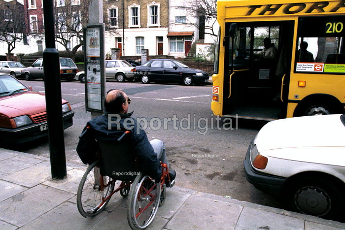 Disabled man in a wheelchair waiting at a bus stop for a bus with disabled access. The bus pictured was unable to pick him up. - Duncan Phillips - 2002-12-02