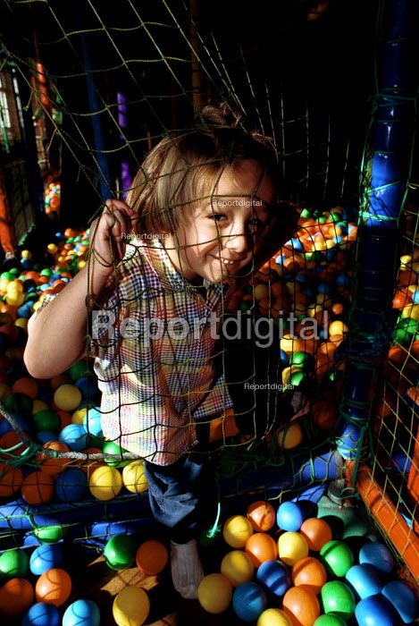 Autistic child playing in a ball pond in a play barn - Duncan Phillips - 1999-04-05