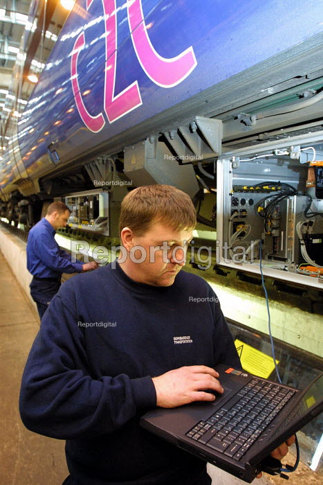 Engineer using laptop computer, involved in the mechanical maintenance on trains prior to being put into service. East Ham Depot, London. - Duncan Phillips - 2003-01-23