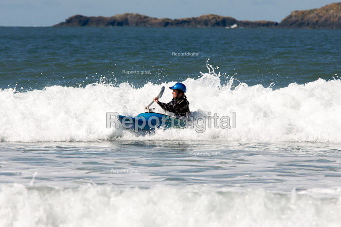 Young woman surfing in canoe Pembrokeshire, Wales - Duncan Phillips - 2009-04-11