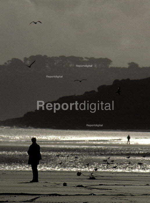 Woman walks alone on a deserted beach in winter. - Duncan Phillips - 2005-07-15
