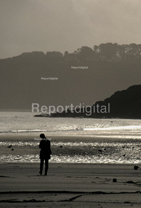 Woman walking alone on a deserted beach in winter - Duncan Phillips - 2005-07-15