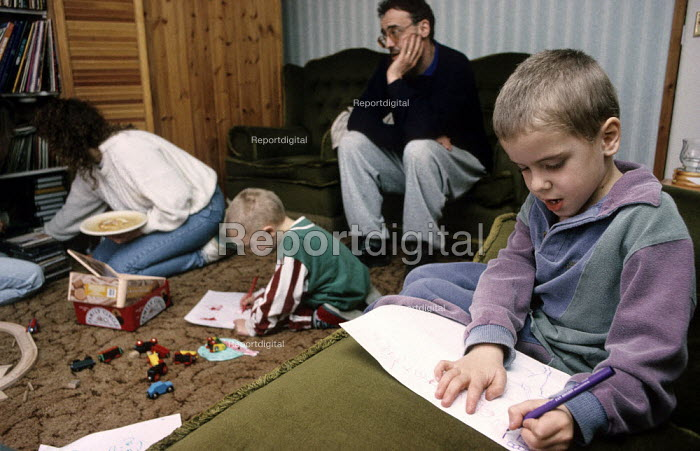 Stressed and tired parents look on as their children draw at home. - Duncan Phillips - 2005-07-15