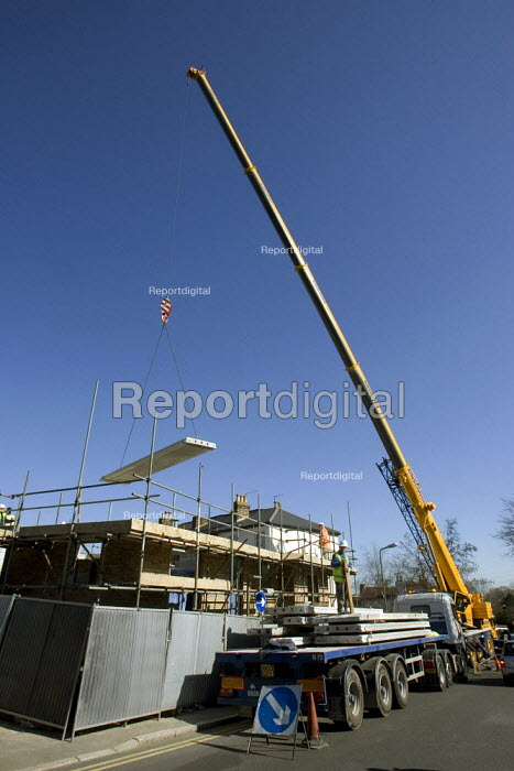 Crane lowering concrete slabs into position for the construction of new flats London - Duncan Phillips - 2006-04-05