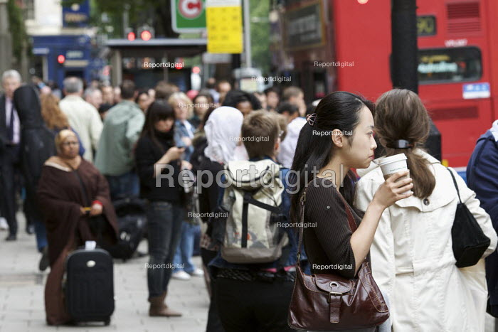 Woman drinking coffee whilst waiting for a bus, London Underground strike. Commuters make alternative travel arrangements due to the closure of much of London Underground by a strike. - Duncan Phillips - 2009-06-10