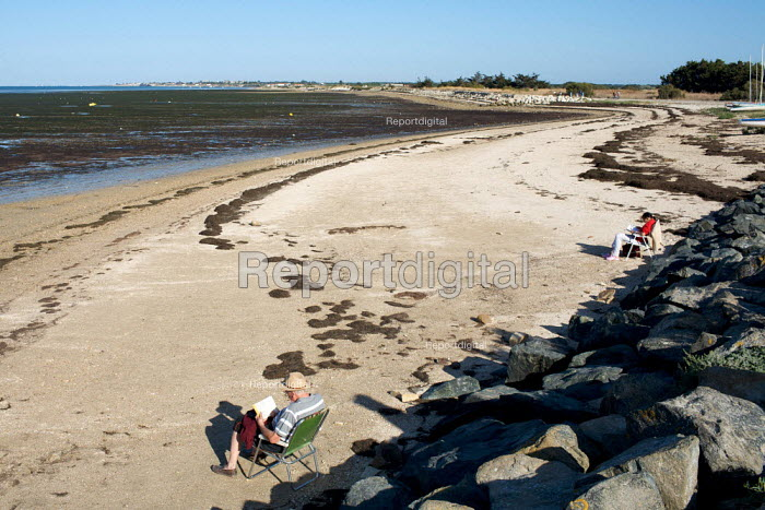 Elderly man and woman reading on a deserted beach, France. - Duncan Phillips - 2009-08-26