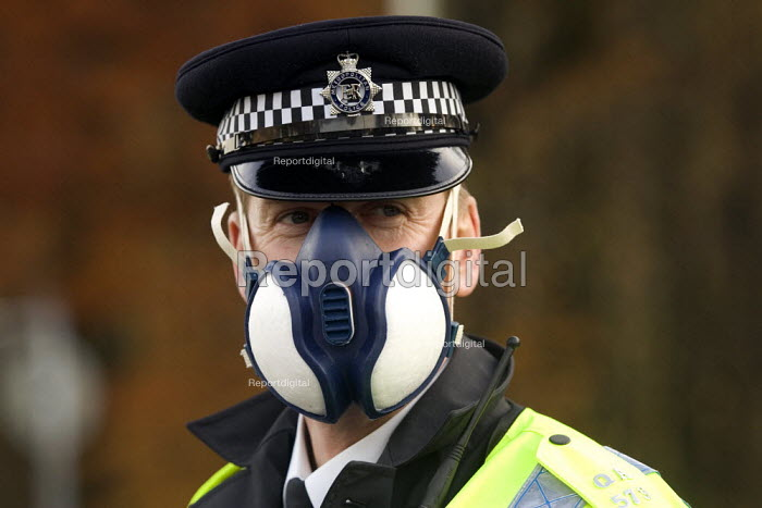 Policeman using face mask for protection from the plume of black smoke from the fire at Buncefield oil depot fire - Duncan Phillips - 2005-12-13