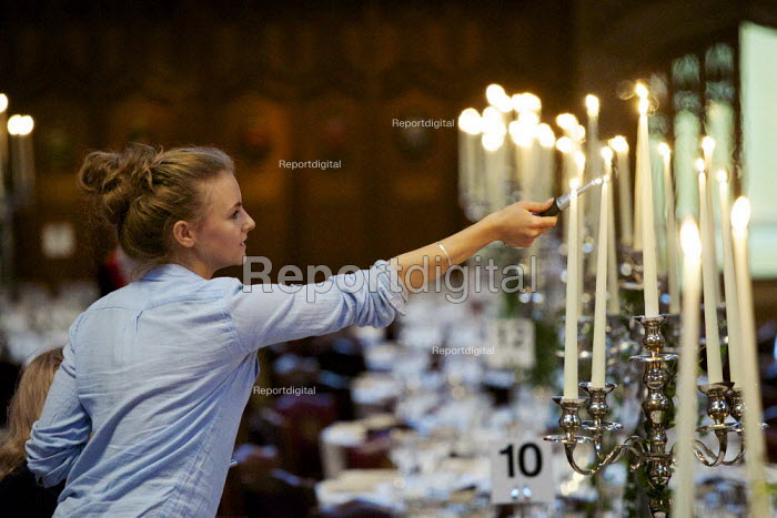 Hospitality worker lighting candles for a formal function, London. - Duncan Phillips - 2015-09-14